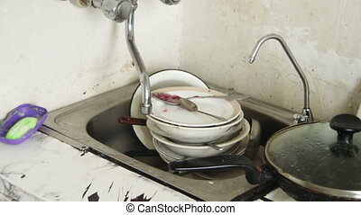 Dirty Dishes in the Sink of the Old Home Kitchen Pile of...