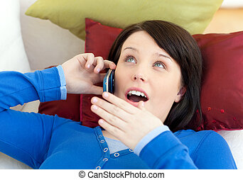 Surprised teen girl talking on phone lying on a sofa