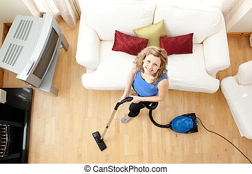 Blond woman cleaning living-room looking at us