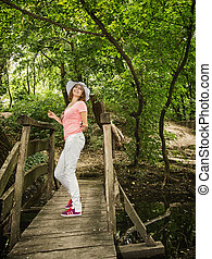 Young youful woman with sunhat posing on the wooden bridge...