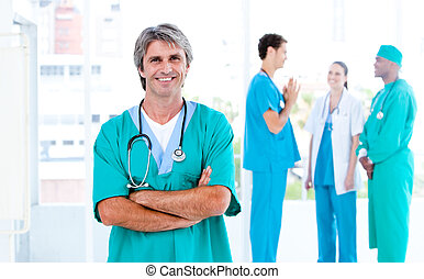 MAture male doctor standing with his team in the background
