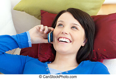 Happy teen girl talking on phone lying on a sofa in the...