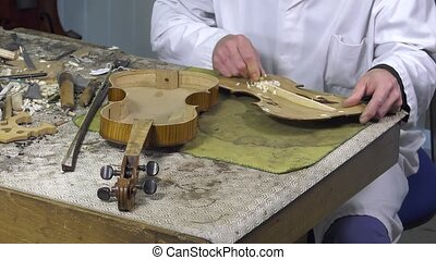 luthier repairs a violin - Luthier forms the harmony bar of...