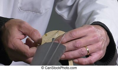 a luthier repairs a cello - Luthier positions the strings on...