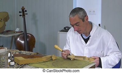 Luthier sculpt a cello head - Shaping volute head using a...