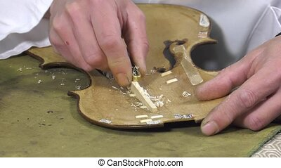 a luthier repairs a violin - Luthier forms the harmony bar...