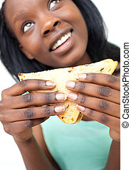 Smiling young woman eating a sandwich