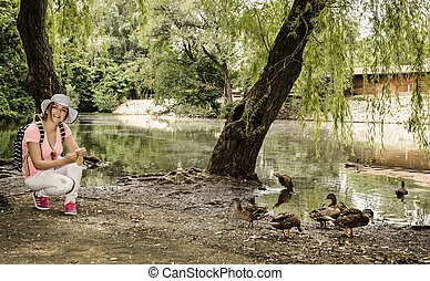 Young woman is feeding the group of duck in the city park...