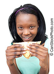 Happy young woman eating a sandwich