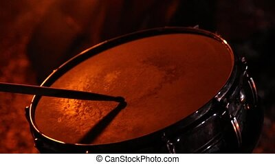 drumsticks knock on the drum, while dancing with fire