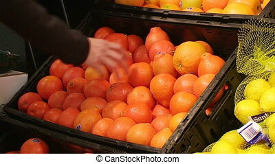Woman Selecting Oranges In Produce - Woman selecting oranges...