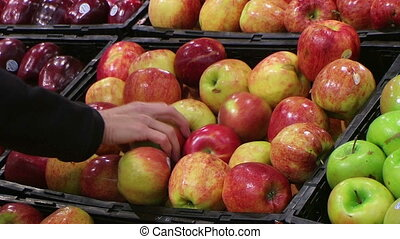 Woman Selecting Apples In Produce - Woman selecting apples...