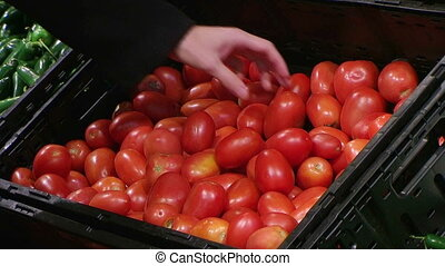 Woman Selecting Tomatoes In Produce - Woman selecting...