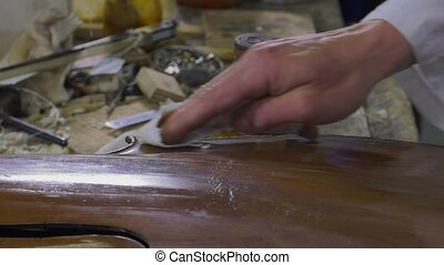 a luthier repairs a cello - Cleaning and polishing an old...