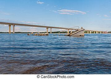 Sinking boat in a river - Rusty sunken vessel in a blue...