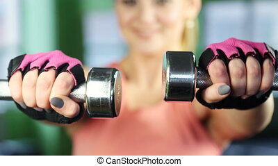 Young happy smiling woman in sportswear, doing fitness exercise with dumbbells