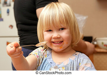 the little blonde girl eats food spoon
