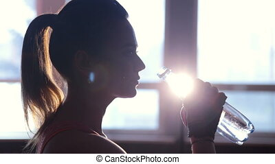Fitness sporty girl silhouette excercising and drinking a...