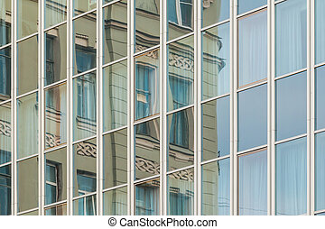 Specular facade with reflection of old building