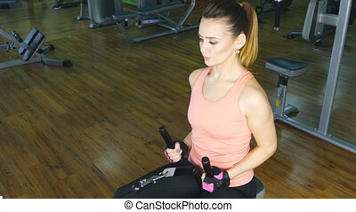 young woman flexing muscles on gym machine - sport, fitness,...