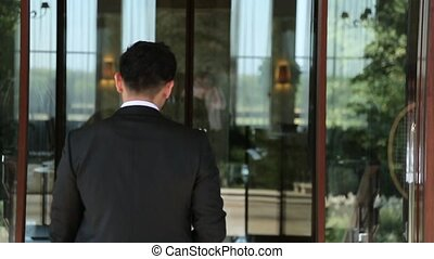 Businessman in a black suit enters the business center