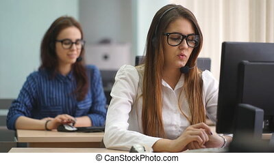 Two women communicate with customers in a call center