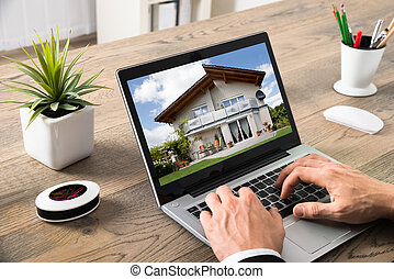 Close-up Of Businessman Looking At House On Computer At Desk...