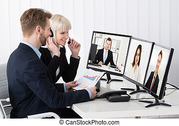Businesspeople Video Conferencing On Desk - Two...