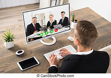 Businessman Attending Videoconference At Office - Young...