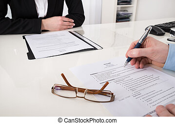 Businessperson With Resume And Pen - Close-up Of...