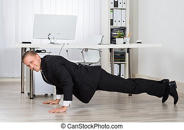 Businessman Doing Pushup At Work - Young Businessman Doing...