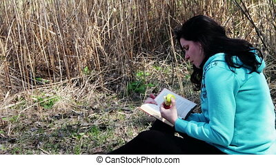 Girl on the Nature of Reading Book Sitting on the Grass in the Forest