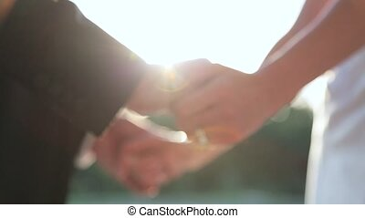 bride and groom holding hands in the sun