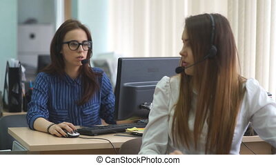 Customer support operator talking in a call center -...