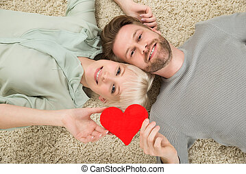 Couple Lying On Carpet Holding Heart