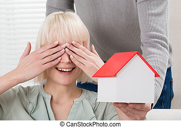 Man Holding House Model In Front Of Smiling Woman