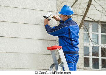 Male Technician Standing On Stepladder Fitting CCTV Camera -...