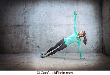 Young woman performing core crunch exercise - slight action...