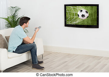 Man Watching Football Match On Television - Young Man...