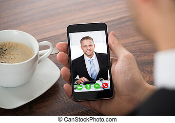 Businessman Videochatting With Colleague On Mobile Phone -...