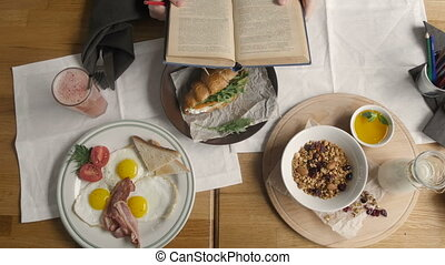 Top View of Healthy Breakfast in Cafe. English breakfast: fried egg, bacon toast on a plate, Croissant with Salmon, Granola and Nuts in Modern Cafe