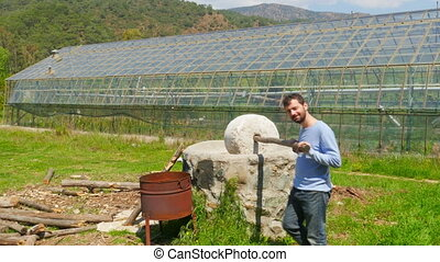 """""""Farmer Man at Traditional mill for crushing plants, background greenhouse"""""""