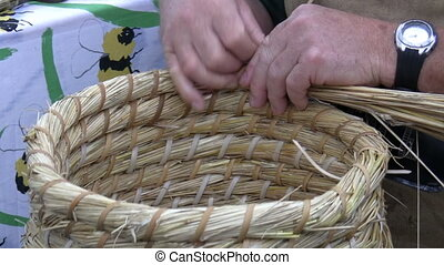 Wheat straw weaving - Artisan weaving a basket using wheat...