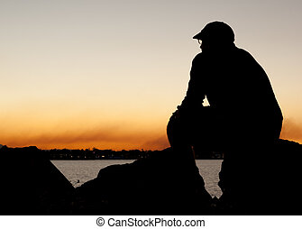 Man in silhouette at sunset - Man in silhouette sitting on...