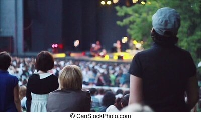 Back side of people at summer live concert Music band...