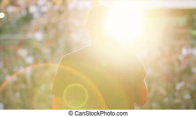 Back side of silhouette man in sun beams perform in...