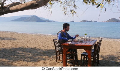Tourist man eating gorgeous breakfast beach with majestic sea background