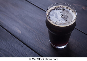 Stout on wood - Nonic pint glass with black stout ale on a...