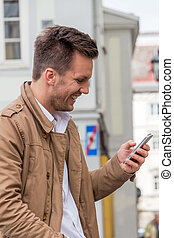 man writing sms - a man writes on his mobile phone an sms....