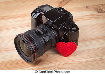 Analog SLR camera with heart on wooden background